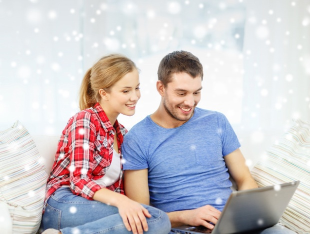 technology, people and relationships concept - smiling couple with laptop computer sitting on sofa at home